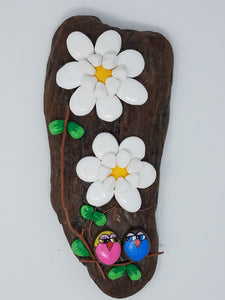 Pebble flowers and owls on driftwood