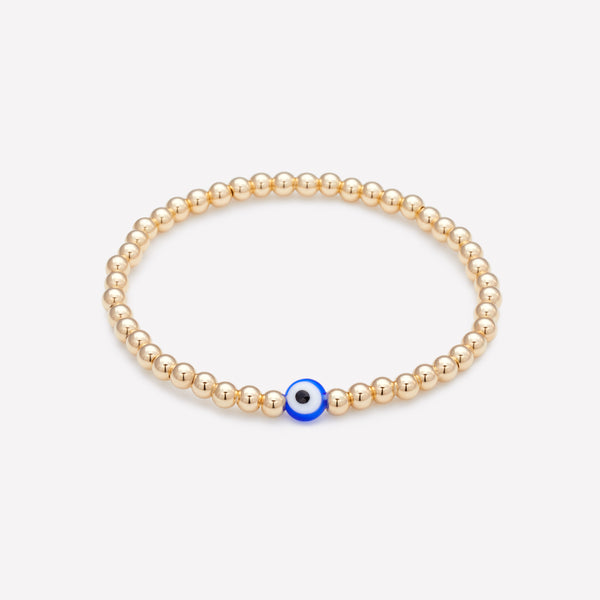 Yellow gold beaded bracelet with blue glass evil eye as seen in vanity fair for women