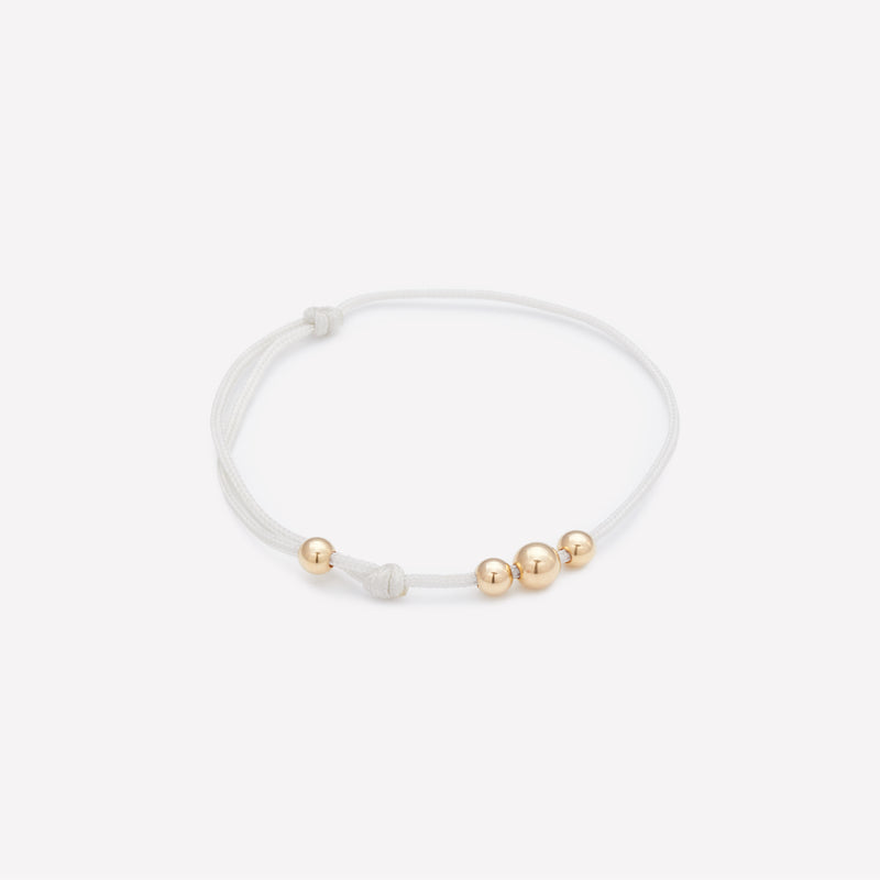 White string bracelet with yellow gold beads for kids
