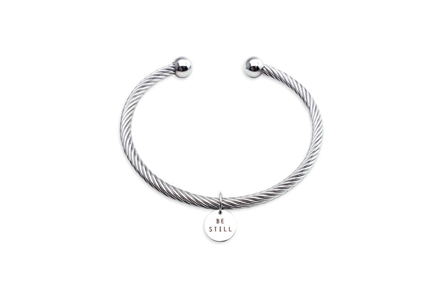 Be Still engraved on round pendant on rope bracelet