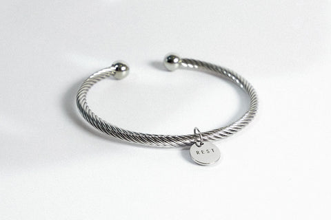 Rope bracelet with engraved pendant rest in silver color