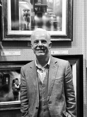 Artist Tim Shorten standing in front of a display of his original paintings and prints at The Acorn Gallery, Pocklington near York.
