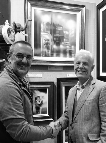 Artist Tim Shorten shaking hands with gallery owner John Wass in front of a display of original paintings and limited edition prints. All artwork available from The Acorn Gallery, Pocklington near York.
