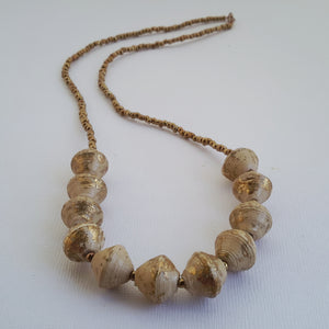 Beige/gold/natural white hand made design paper bead necklace made out of recycled paper in Uganda by principles of fair trade, ethical and sustainable fashion, empowering women of post war area, by Finnish / Scandinavian brand, Agulu Paper Beads. Eettinen luonnonvalkoinen kultakoristeltu käsintehty design paperihelmi-kaulakoru, joka on tehty kierrätyspaperista reilun kaupan periaattein työllistämällä kehitysmaan nasia.
