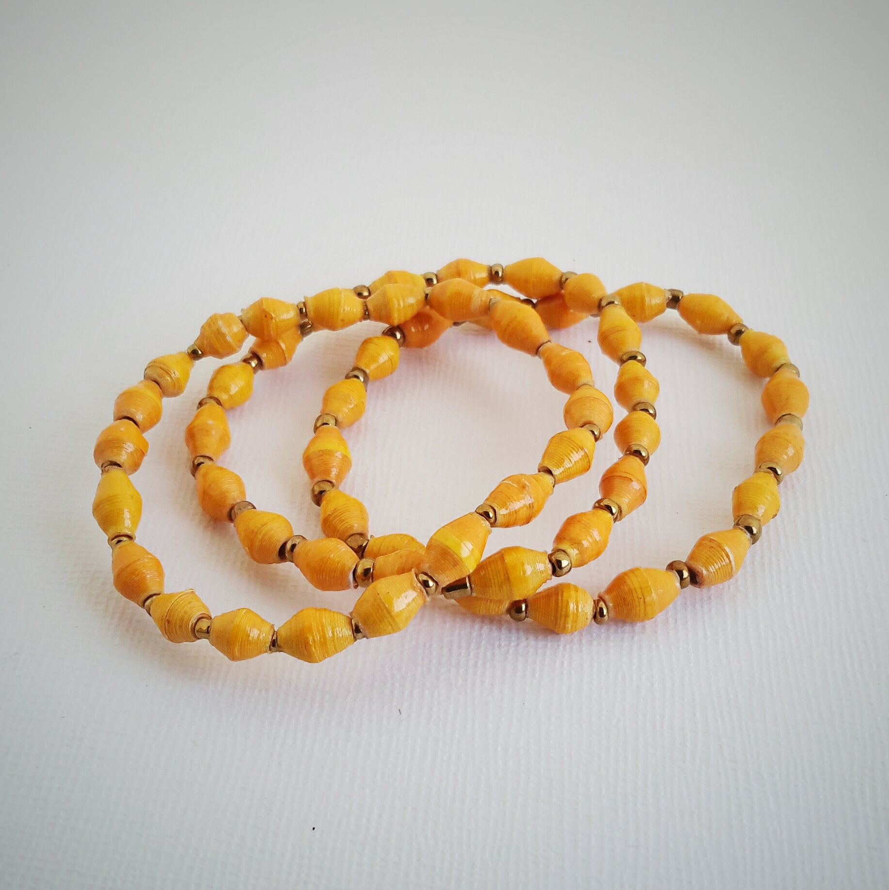 Yellow hand made design paper bead bracelets made out of recycled paper in Uganda by principles of fair trade, ethical and sustainable fashion, empowering women of post war area, by Finnish / Scandinavian brand, Agulu Paper Beads. Eettiset keltaiset käsintehdyt design rannekorut, jotka on tehty kierrätyspaperista reilun kaupan periaattein työllistämällä kehitysmaan nasia.