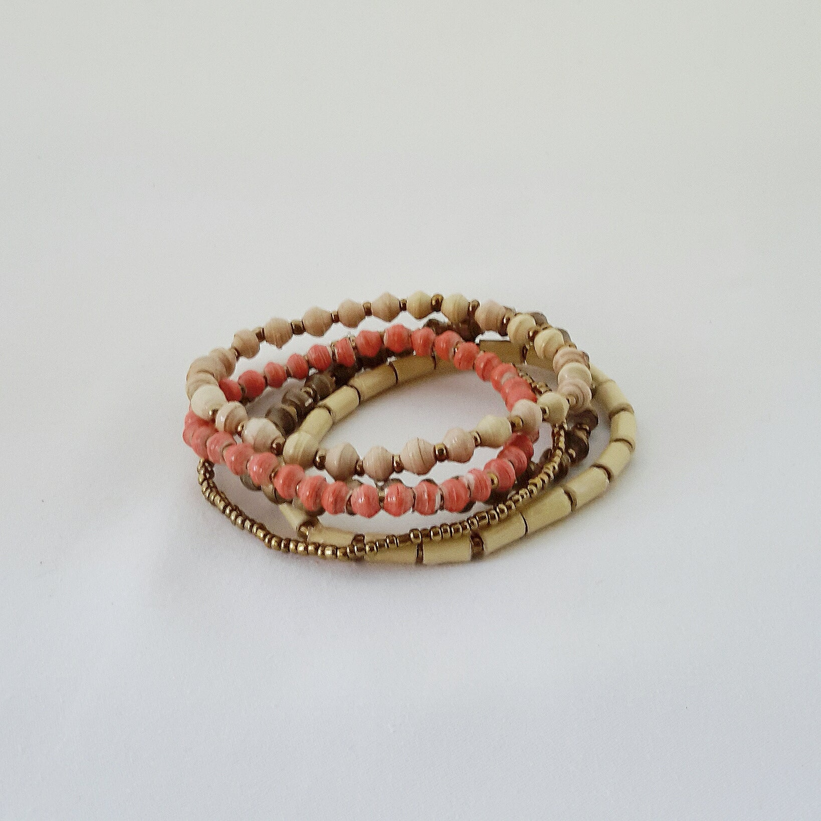 Coral pink ethical hand made design paper bead bracelet made out of recycled paper in Uganda by principles of fair trade, ethical and sustainable fashion, empowering women of post war area, by Finnish / Scandinavian brand, Agulu Paper Beads. Eettinen korallinpunainen käsintehty design rannekoru, joka on tehty kierrätyspaperista reilun kaupan periaattein työllistämällä Ugandalaisia nasia.