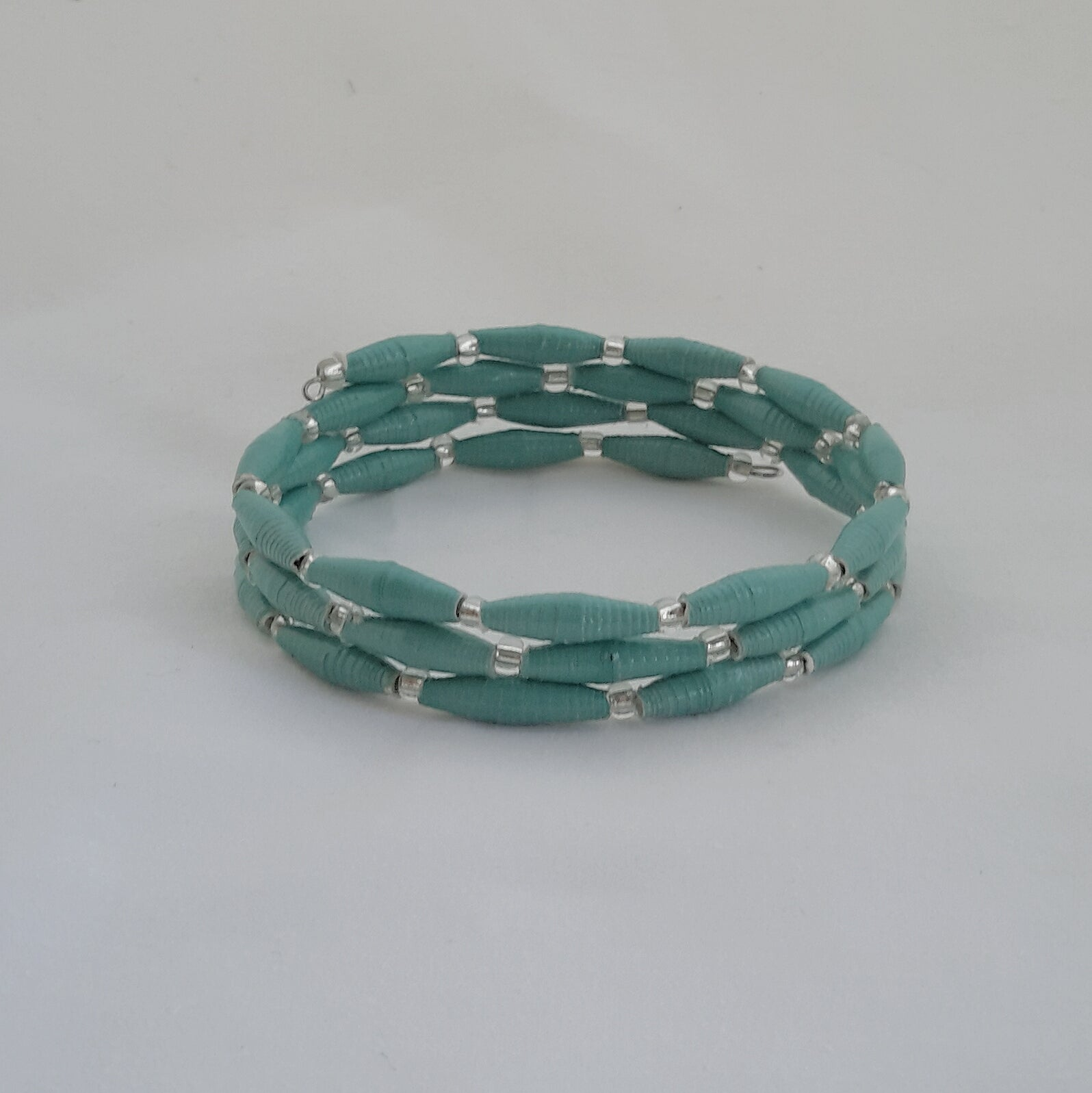 Aquamarine/turquoise hand made design paper bead bracelet made out of recycled paper in Uganda by principles of fair trade, ethical and sustainable fashion, empowering women of post war area, by Finnish / Scandinavian brand, Agulu Paper Beads. Eettinen turkoosi/vedenvihreä käsintehty design rannekoru, joka on tehty kierrätyspaperista reilun kaupan periaattein työllistämällä kehitysmaan nasia.