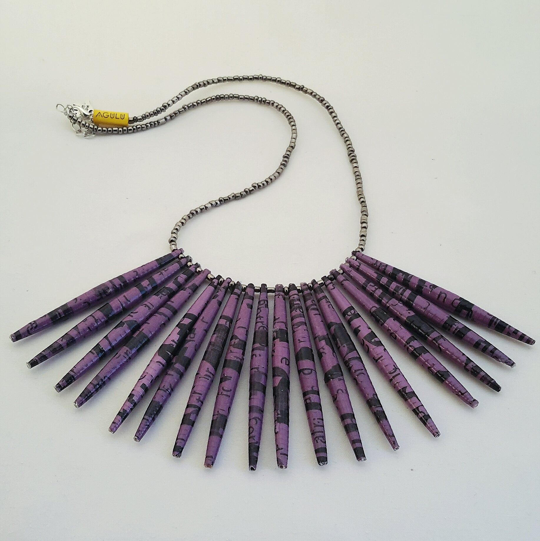 Purple / Violet hand made design paper bead necklace made out of recycled paper in Uganda by principles of fair trade, ethical and sustainable fashion, empowering women of post war area, by Finnish / Scandinavian brand, Agulu Paper Beads. Eettinen lila / violetti käsintehty design kaulakoru, joka on tehty kierrätyspaperista reilun kaupan periaattein työllistämällä kehitysmaan nasia.