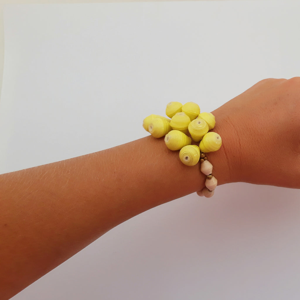 Yellow hand made design paper bead bracelet made out of recycled paper in Uganda by principles of fair trade, ethical and sustainable fashion, empowering women of post war area, by Finnish / Scandinavian brand, Agulu Paper Beads. Eettinen keltainen käsintehty design rannekoru, jota on tehty kierrätyspaperista reilun kaupan periaattein työllistämällä kehitysmaan nasia.