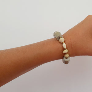 Natural white/gold/grey hand made design paper bead bracelet made out of recycled paper in Uganda by principles of fair trade, ethical and sustainable fashion, empowering women of post war area, by Finnish / Scandinavian brand, Agulu Paper Beads. Eettinen luonnonvalkoinen/kultainen/harmaa käsintehty design rannekoru, jota on tehty kierrätyspaperista reilun kaupan periaattein työllistämällä kehitysmaan nasia.