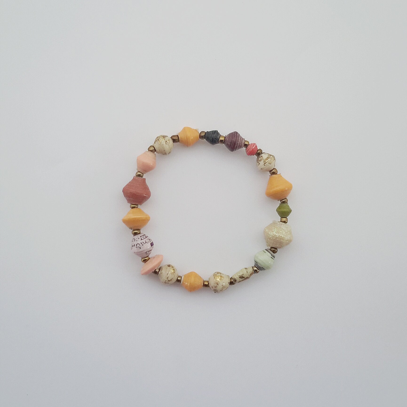 Hand made design bracelet with paper beads of different natural colors made out of recycled paper in Uganda by principles of fair trade, ethical and sustainable fashion, empowering women of post war area, by Finnish / Scandinavian brand, Agulu Paper Beads. Eettinen käsintehty design rannekoru luonnonläheisillä väreillä olevista paperihelmistä, jotka on tehty kierrätyspaperista reilun kaupan periaattein työllistämällä kehitysmaan nasia.