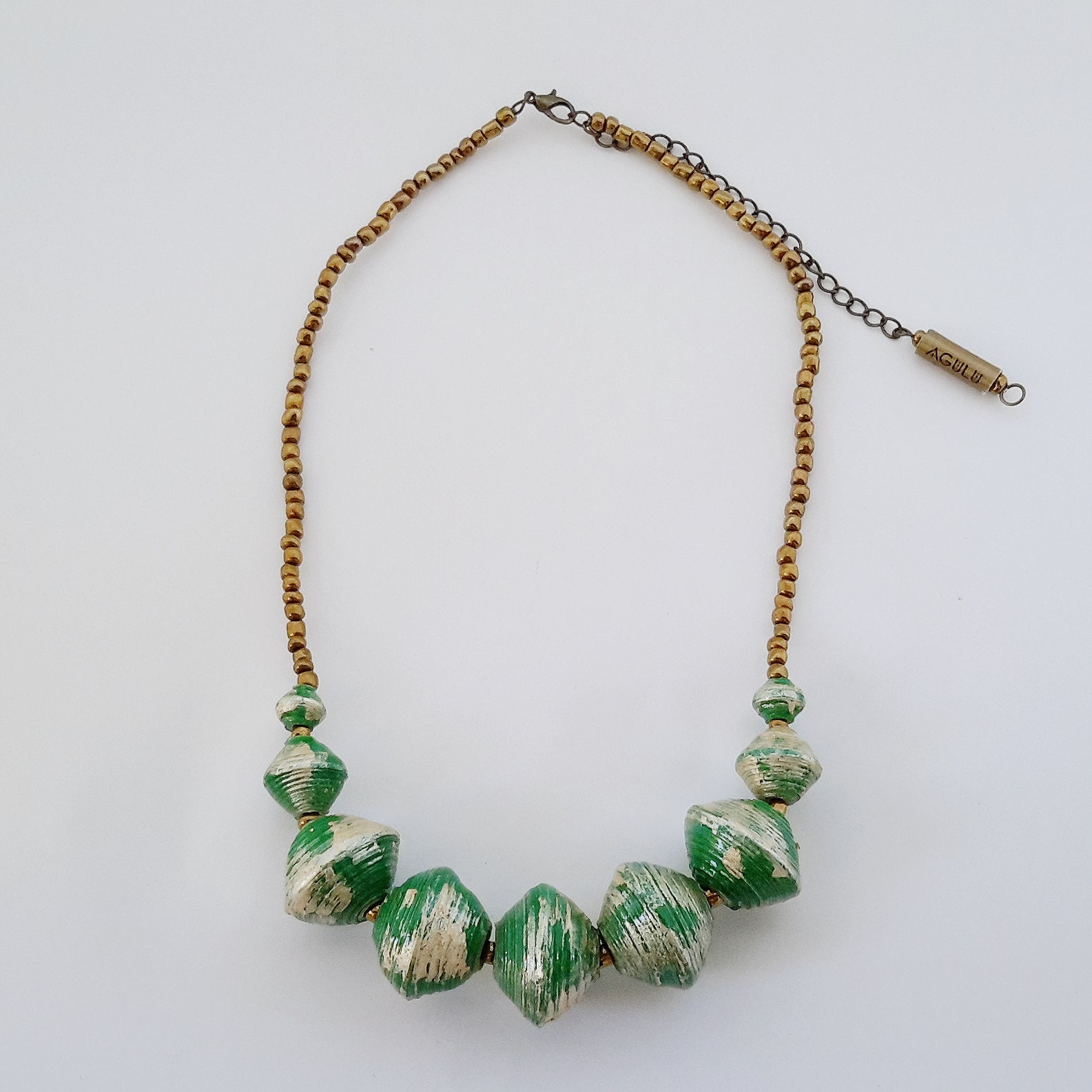 Green hand made ethical design paper bead necklace made out of recycled paper in Uganda by principles of fair trade, ethical and sustainable fashion, empowering women of post war area, by Finnish / Scandinavian brand, Agulu Paper Beads. Eettinen vihreä käsintehty design kaulakoru, joka on tehty kierrätyspaperista reilun kaupan periaattein työllistämällä kehitysmaan nasia.