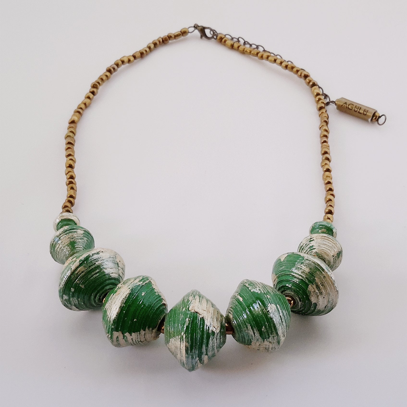 Green hand made ethical design paper bead necklace made out of recycled paper in Uganda by principles of fair trade, ethical and sustainable fashion, empowering women of post war area, by Finnish / Scandinavian brand, Agulu Paper Beads. Eettinen vihreä käsintehty design kaulakoru, joka on tehty kierrätyspaperista reilun kaupan periaattein työllistämällä Ugandalaisia nasia.