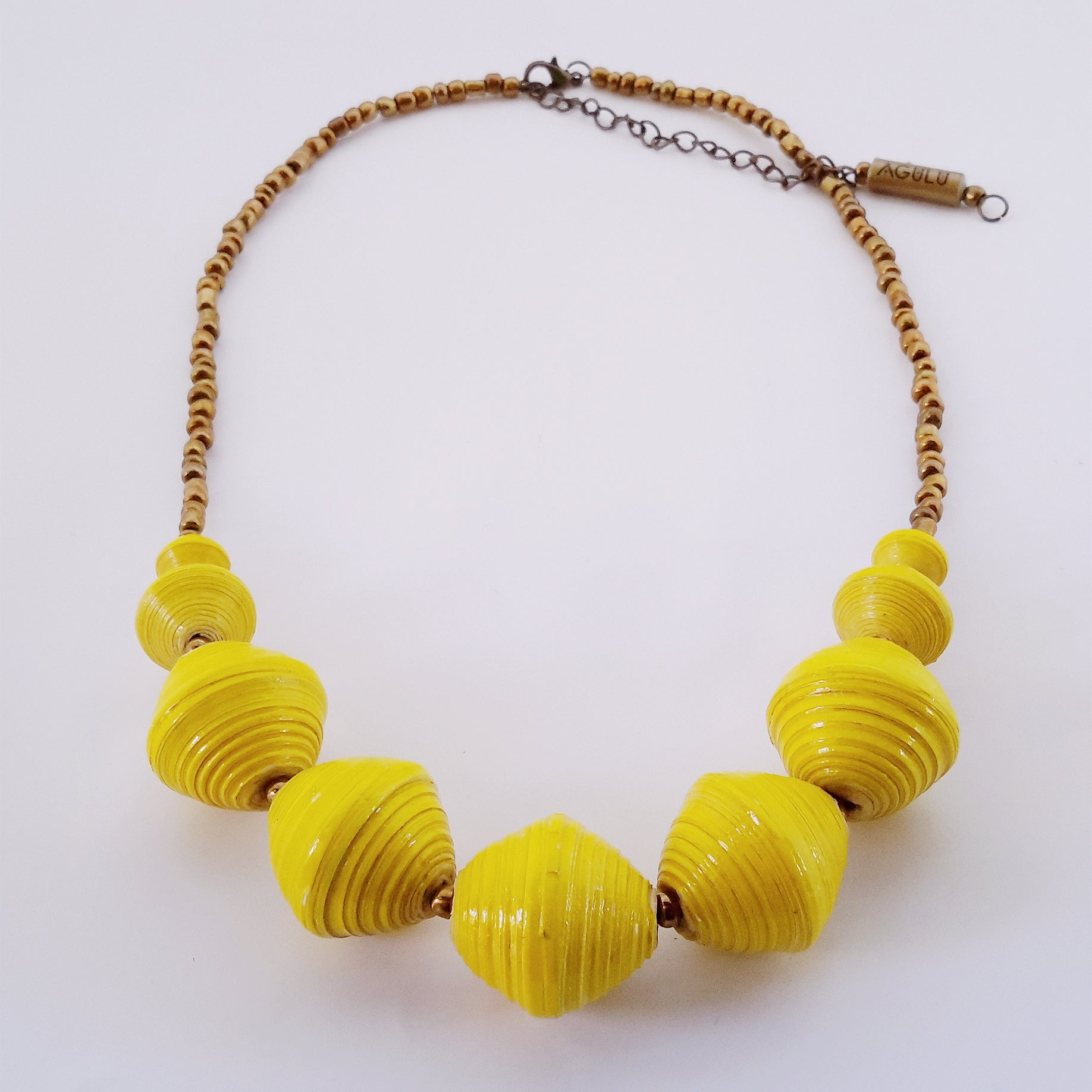 Yellow hand made ethical design paper bead necklace made out of recycled paper in Uganda by principles of fair trade, ethical and sustainable fashion, empowering women of post war area, by Finnish / Scandinavian brand, Agulu Paper Beads. Eettinen keltainen käsintehty design kaulakoru, joka on tehty kierrätyspaperista reilun kaupan periaattein työllistämällä kehitysmaan nasia.