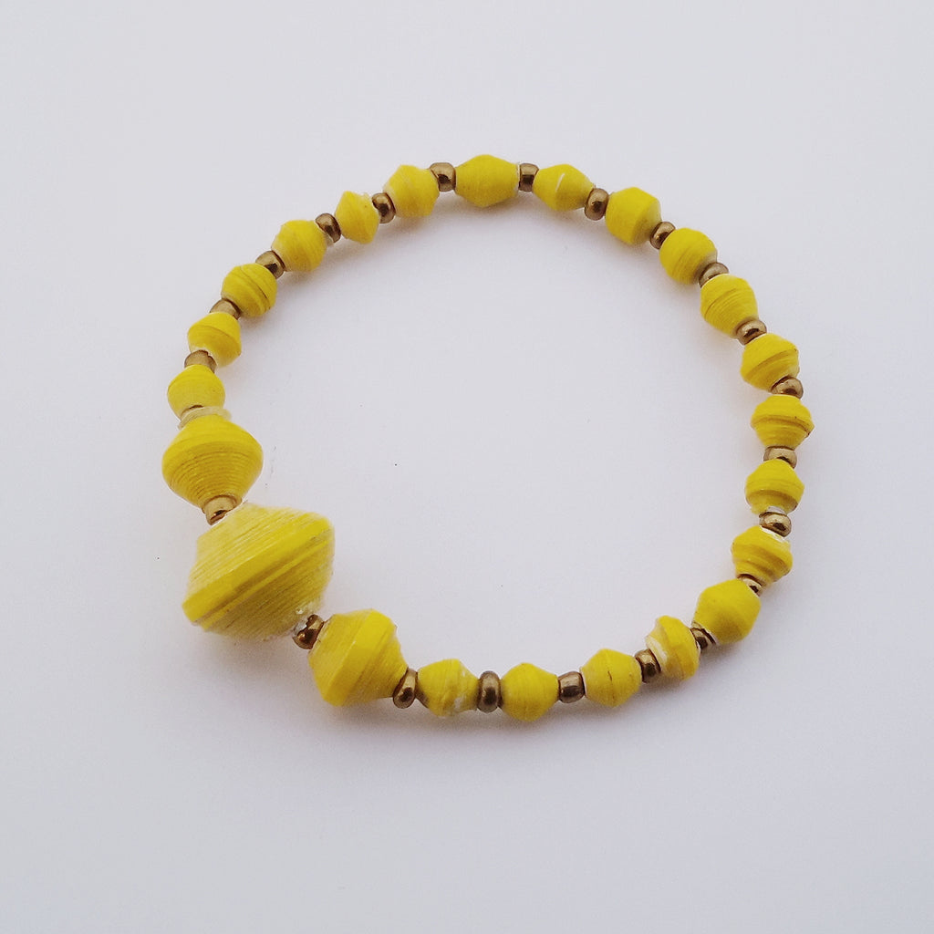 Yellow hand made ethical design paper bead bracelet made out of recycled paper in Uganda by principles of fair trade, ethical and sustainable fashion, empowering women of post war area, by Finnish / Scandinavian brand, Agulu Paper Beads. Eettinen keltainen käsintehty design rannekoru, joka on tehty kierrätyspaperista reilun kaupan periaattein työllistämällä kehitysmaan nasia.