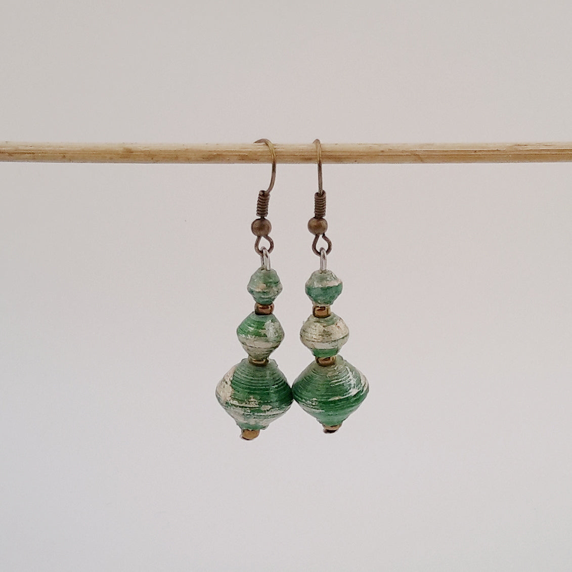Green hand made ethical design paper bead earrings made out of recycled paper in Uganda by principles of fair trade, ethical and sustainable fashion, empowering women of post war area, by Finnish / Scandinavian brand, Agulu Paper Beads. Eettiset vihreät käsintehdyt design korvakorut, joka on tehty kierrätyspaperista reilun kaupan periaattein työllistämällä kehitysmaan nasia.