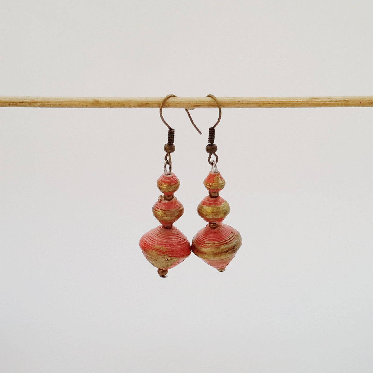 Orange hand made ethical design paper bead earrings made out of recycled paper in Uganda by principles of fair trade, ethical and sustainable fashion, empowering women of post war area, by Finnish / Scandinavian brand, Agulu Paper Beads. Eettiset oranssit käsintehdyt design korvakorut, joka on tehty kierrätyspaperista reilun kaupan periaattein työllistämällä kehitysmaan nasia.