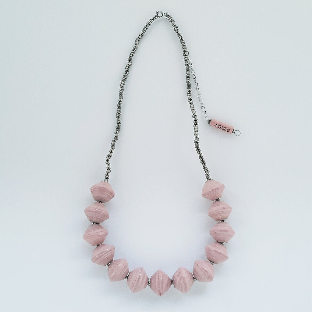 Ethical pink hand made design paper bead necklace made out of recycled paper in Uganda by principles of fair trade, ethical and sustainable fashion, empowering women of post war area, by Finnish / Scandinavian brand, Agulu Paper Beads. Eettinen vaaleanpunainen käsintehty design paperihelmikaulakoru, joka on tehty kierrätyspaperista reilun kaupan periaattein työllistämällä kehitysmaan nasia.