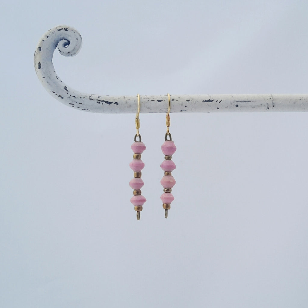Pink hand made ethical design paper bead earrings made out of recycled paper in Uganda by principles of fair trade, ethical and sustainable fashion, empowering women of post war area, by Finnish / Scandinavian brand, Agulu Paper Beads. Eettiset vaaleanpunaiset käsintehdyt design korvakorut, jotka on tehty kierrätyspaperista reilun kaupan periaattein työllistämällä kehitysmaan nasia.