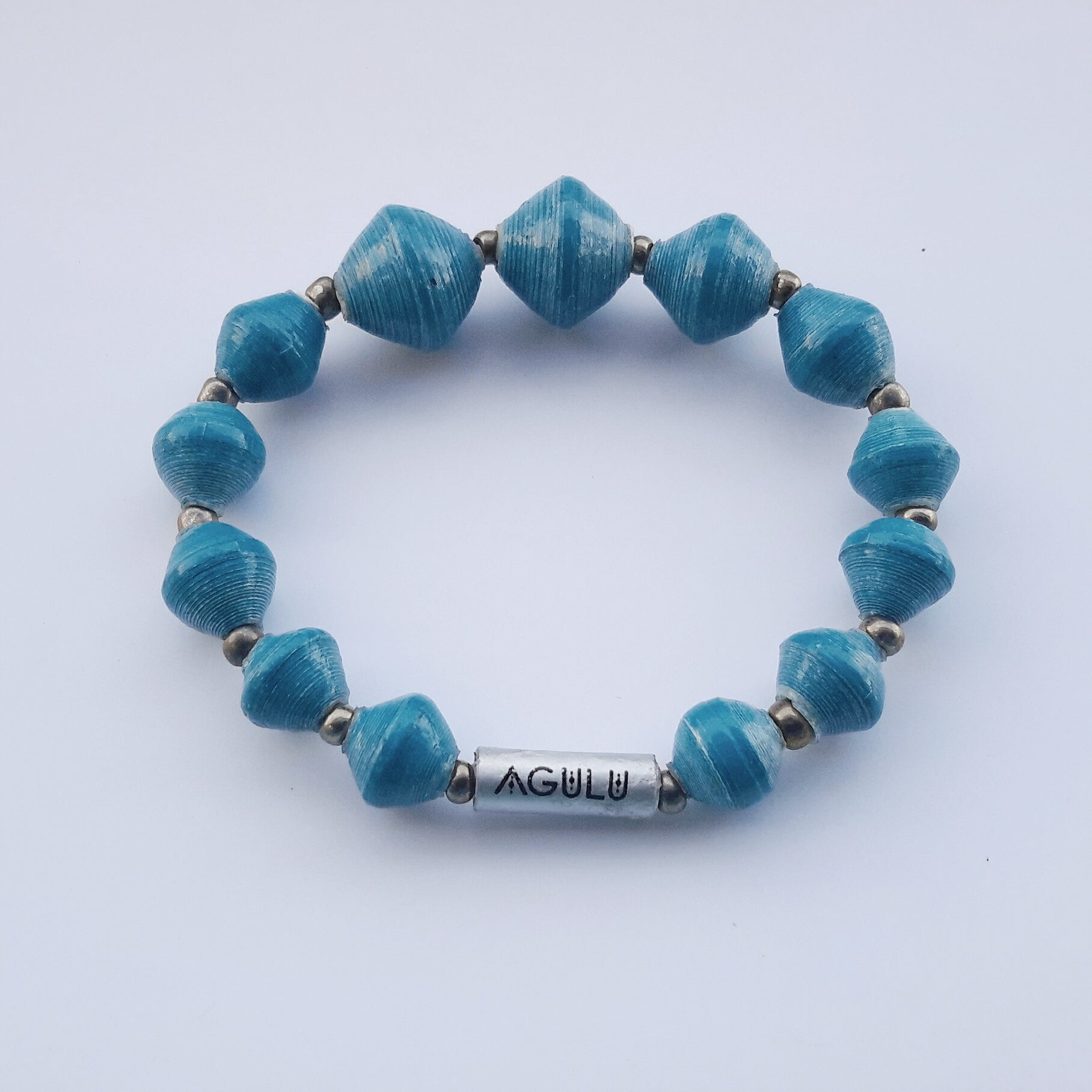 Prussian blue/teal blue/turquoise hand made ethical design paper bead bracelet made out of recycled paper in Uganda by principles of fair trade, ethical and sustainable fashion, empowering women of post war area, by Finnish / Scandinavian brand, Agulu Paper Beads. Eettinen petroolinsininen/turkoosi käsintehty design rannekoru, joka on tehty kierrätyspaperista reilun kaupan periaattein työllistämällä Ugandalaisia nasia.