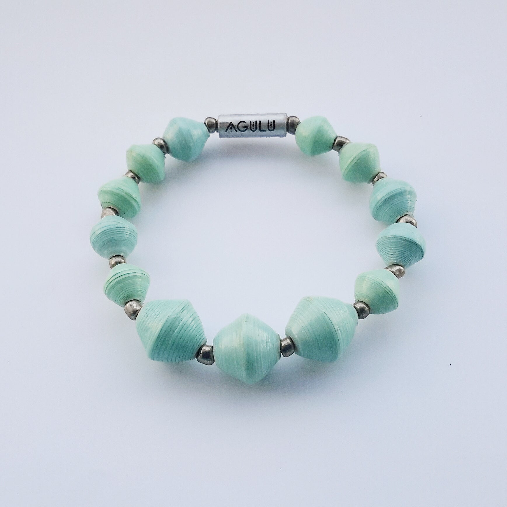 Aquamarine/turquoise hand made ethical design paper bead bracelet made out of recycled paper in Uganda by principles of fair trade, ethical and sustainable fashion, empowering women of post war area, by Finnish / Scandinavian brand, Agulu Paper Beads. Eettinen vedenvihreä/turkoosi käsintehty design rannekoru, joka on tehty kierrätyspaperista reilun kaupan periaattein työllistämällä Ugandalaisia nasia.