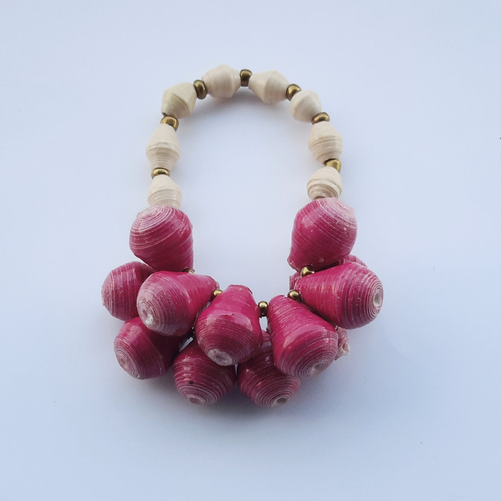 Rasberry pink hand made design paper bead bracelet made out of recycled paper in Uganda by principles of fair trade, ethical and sustainable fashion, empowering women of post war area, by Finnish / Scandinavian brand, Agulu Paper Beads. Eettinen vadelmanpunainen käsintehty design rannekoru, jota on tehty kierrätyspaperista reilun kaupan periaattein työllistämällä Ugandalaisia nasia.