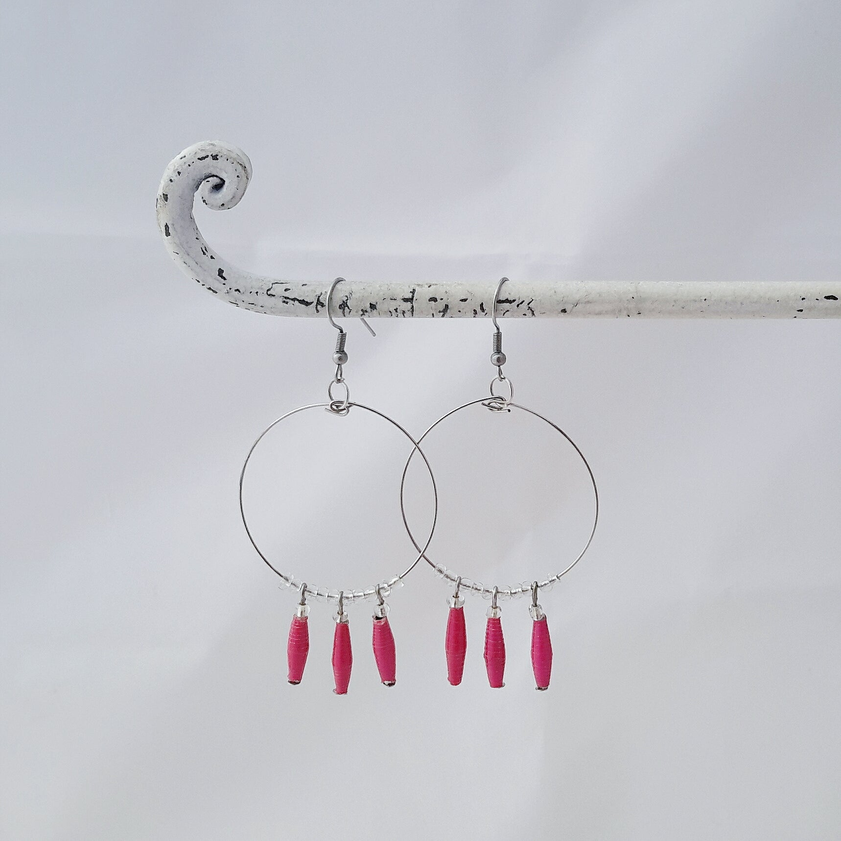 Hand made pink design paper bead earrings made out of recycled paper in Uganda by principles of fair trade, ethical and sustainable fashion, empowering women of post war area, by Finnish / Scandinavian brand, Agulu Paper Beads. Eettiset käsintehdyt pinkit design paperihelmikorvakorut, jotka on tehty reilun kaupan periaattein työllistämällä kehitysmaan nasia.