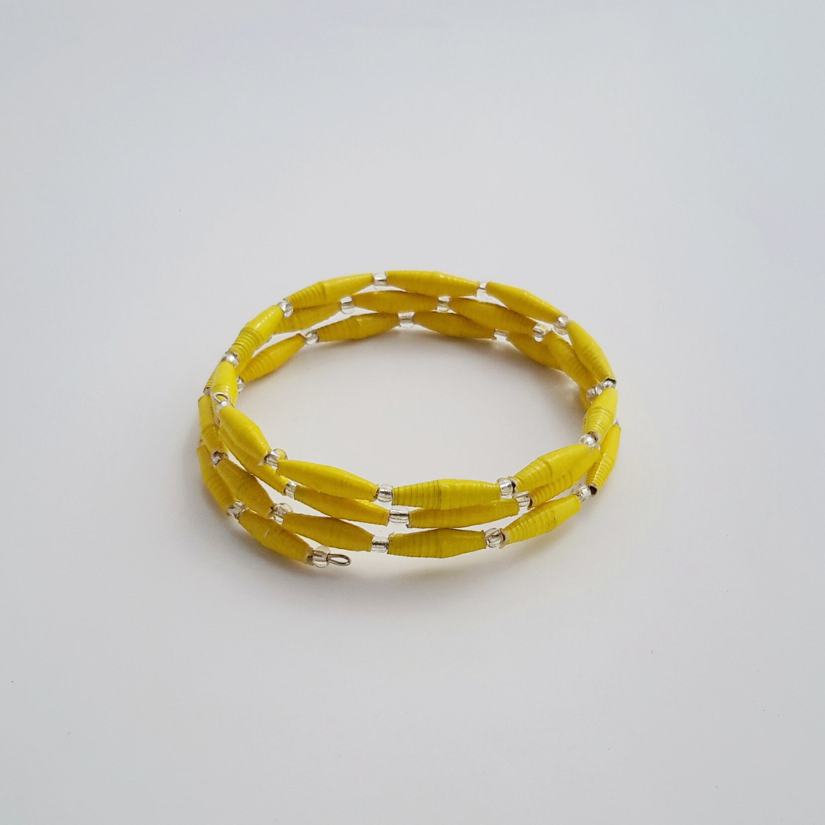 Hand made yellow design paper bead bracelet made out of recycled paper in Uganda by principles of fair trade, ethical and sustainable fashion, by Finnish brand, Agulu Paper Beads. Eettinen keltainen käsintehty design rannekoru, joka on tehty kierrätyspaperista reilun kaupan periaattein työllistämällä Ugandalaisia naisia.