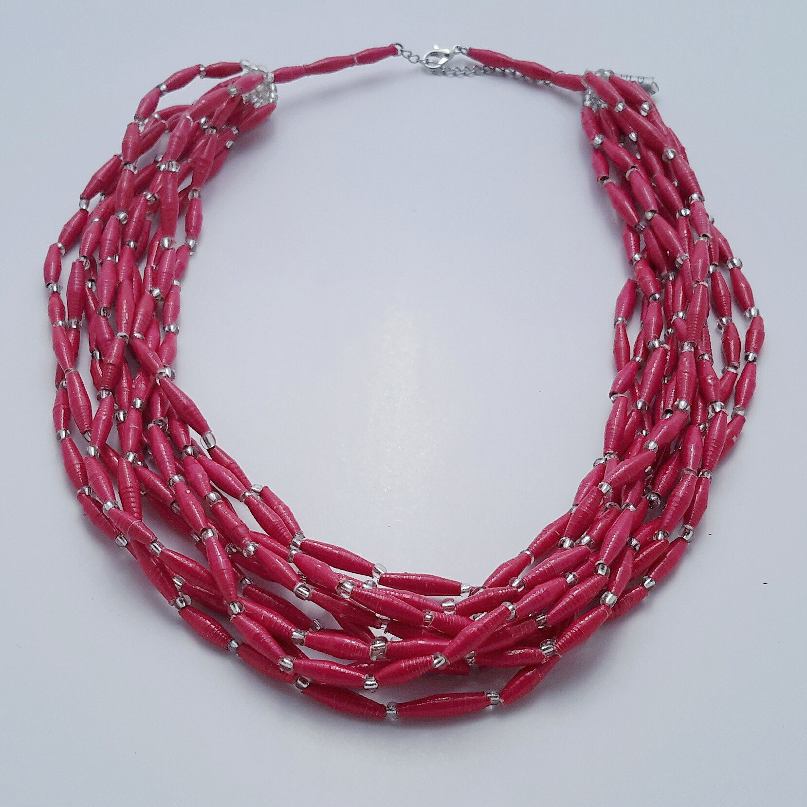 Hand made pink design paper bead necklace made out of recycled paper in Uganda by principles of fair trade, ethical and sustainable fashion, by Finnish brand, Agulu Paper Beads. Eettinen käsintehty pinkki design kaulakoru, joka on tehty kierrätyspaperista reilun kaupan periaattein työllistämällä Ugandalaisia naisia.
