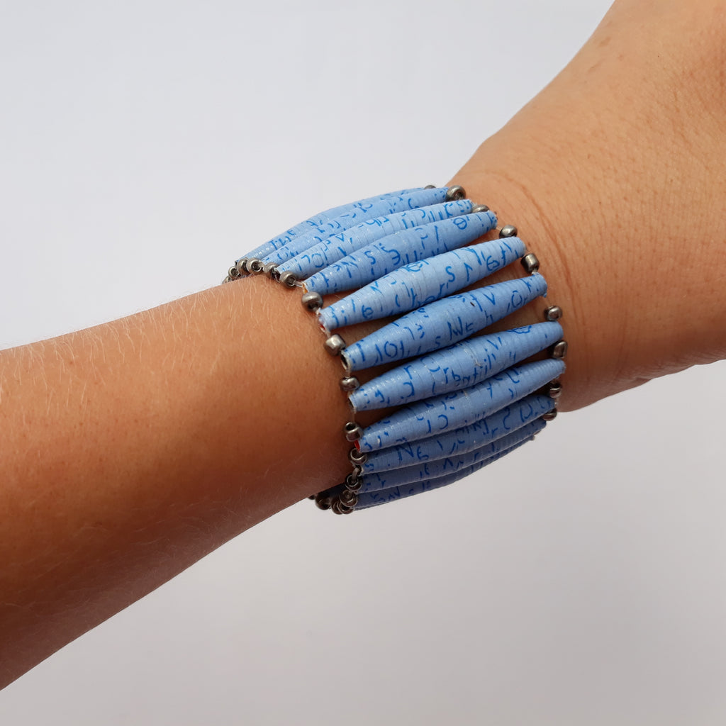 Light blue hand made design paper bead bracelet made out of recycled paper in Uganda by principles of fair trade, ethical and sustainable fashion, empowering women of post war area, by Finnish / Scandinavian brand, Agulu Paper Beads. Eettinen vaaleansininen käsintehty design rannekoru, joka on tehty kierrätyspaperista reilun kaupan periaattein työllistämällä kehitysmaan nasia.
