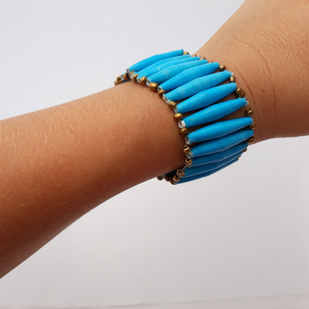 Turquoise hand made design paper bead bracelet made out of recycled paper in Uganda by principles of fair trade, ethical and sustainable fashion, empowering women of post war area, by Finnish / Scandinavian brand, Agulu Paper Beads. Eettinen turkoosi käsintehty design rannekoru, joka on tehty kierrätyspaperista reilun kaupan periaattein työllistämällä kehitysmaan nasia.