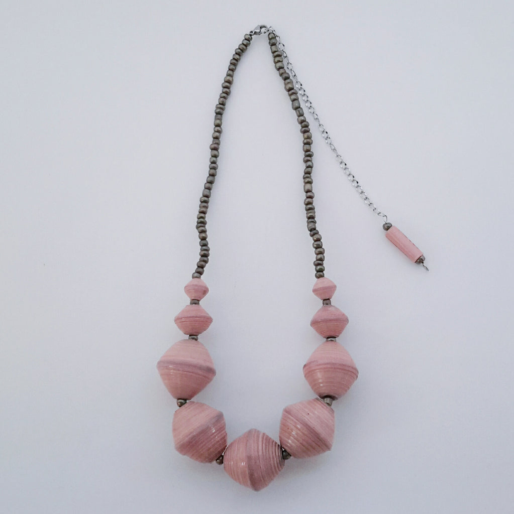 Light blue pink made ethical design paper bead necklace made out of recycled paper in Uganda by principles of fair trade, ethical and sustainable fashion, empowering women of post war area, by Finnish / Scandinavian brand, Agulu Paper Beads. Eettinen vaaleanpunainen käsintehty design kaulakoru, joka on tehty kierrätyspaperista reilun kaupan periaattein työllistämällä Ugandalaisia naisia.