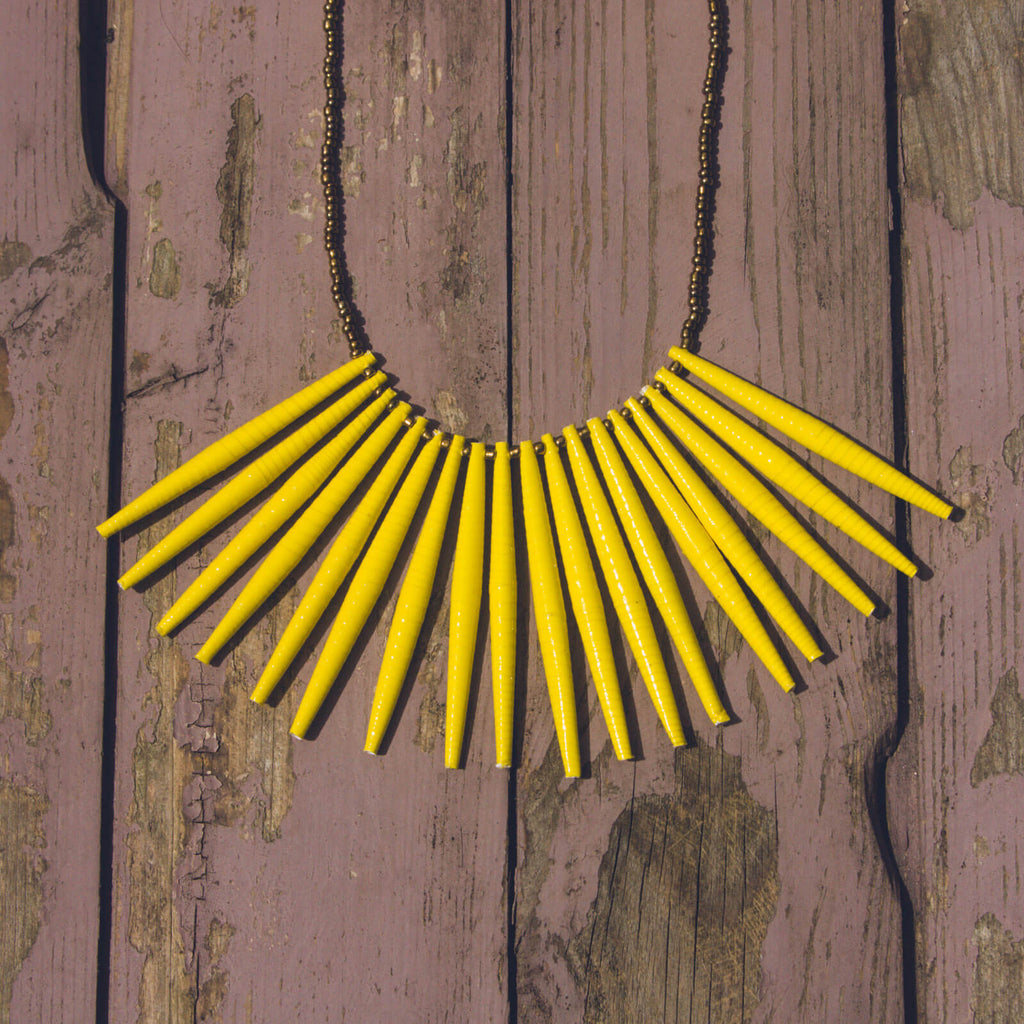 Yellow hand made design paper bead necklace made out of recycled paper in Uganda by principles of fair trade, ethical and sustainable fashion, empowering women of post war area, by Finnish / Scandinavian brand, Agulu Paper Beads. Eettinen keltainen käsintehty design kaulakoru, joka on tehty kierrätyspaperista reilun kaupan periaattein työllistämällä kehitysmaan nasia.