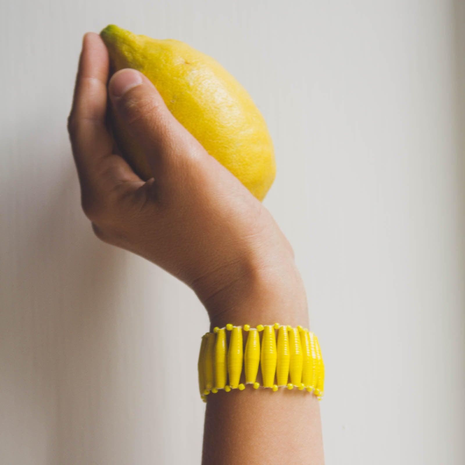 Yellow hand made design paper bead bracelet made out of recycled paper in Uganda by principles of fair trade, ethical and sustainable fashion, empowering women of post war area, by Finnish / Scandinavian brand, Agulu Paper Beads. Eettinen keltainen käsintehty design rannekoru, joka on tehty kierrätyspaperista reilun kaupan periaattein työllistämällä kehitysmaan nasia.