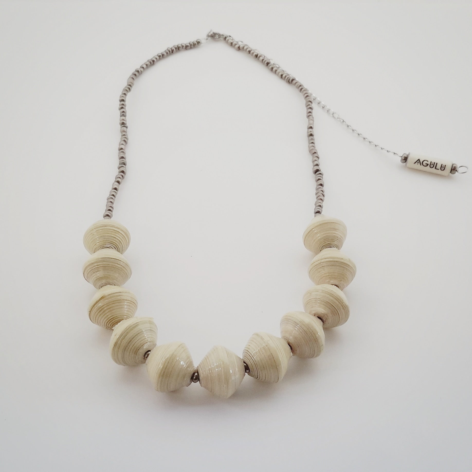 Natural white hand made ethical design paper bead necklace made out of recycled paper in Uganda by principles of fair trade, ethical and sustainable fashion, empowering women of post war area, by Finnish / Scandinavian brand, Agulu Paper Beads. Eettinen luonnonvalkoinen käsintehty design kaulakoru, joka on tehty kierrätyspaperista reilun kaupan periaattein työllistämällä Ugandalaisia nasia.