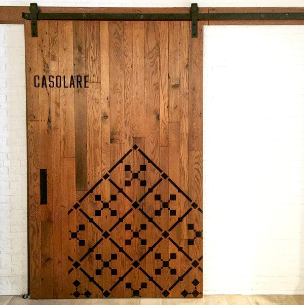 A large laser engraved reclaimed wood barn door for the restaurant casolare