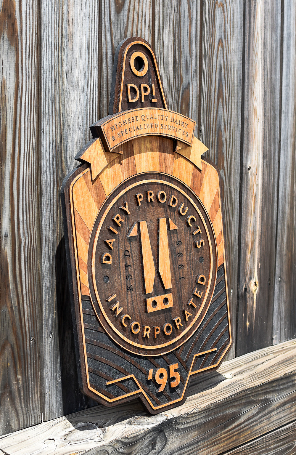 Multi layer, laser cut and engraved, reclaimed walnut, cherry, and white oak sign for dairy products incorporated