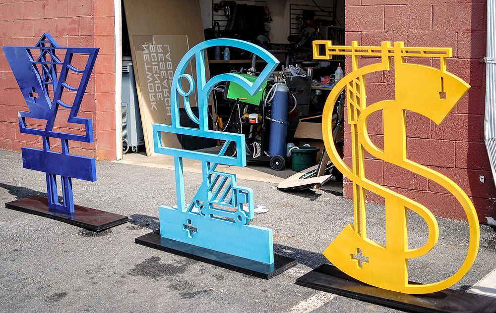 4 foot tall wooden currency symbols. used as stage dressing for the world bank.
