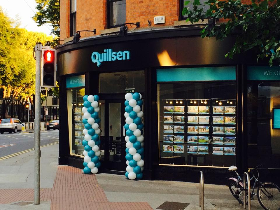 White and teal coloured balloon columns at entrance to building.