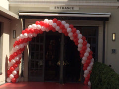 Large red and white balloon arch over doorway.