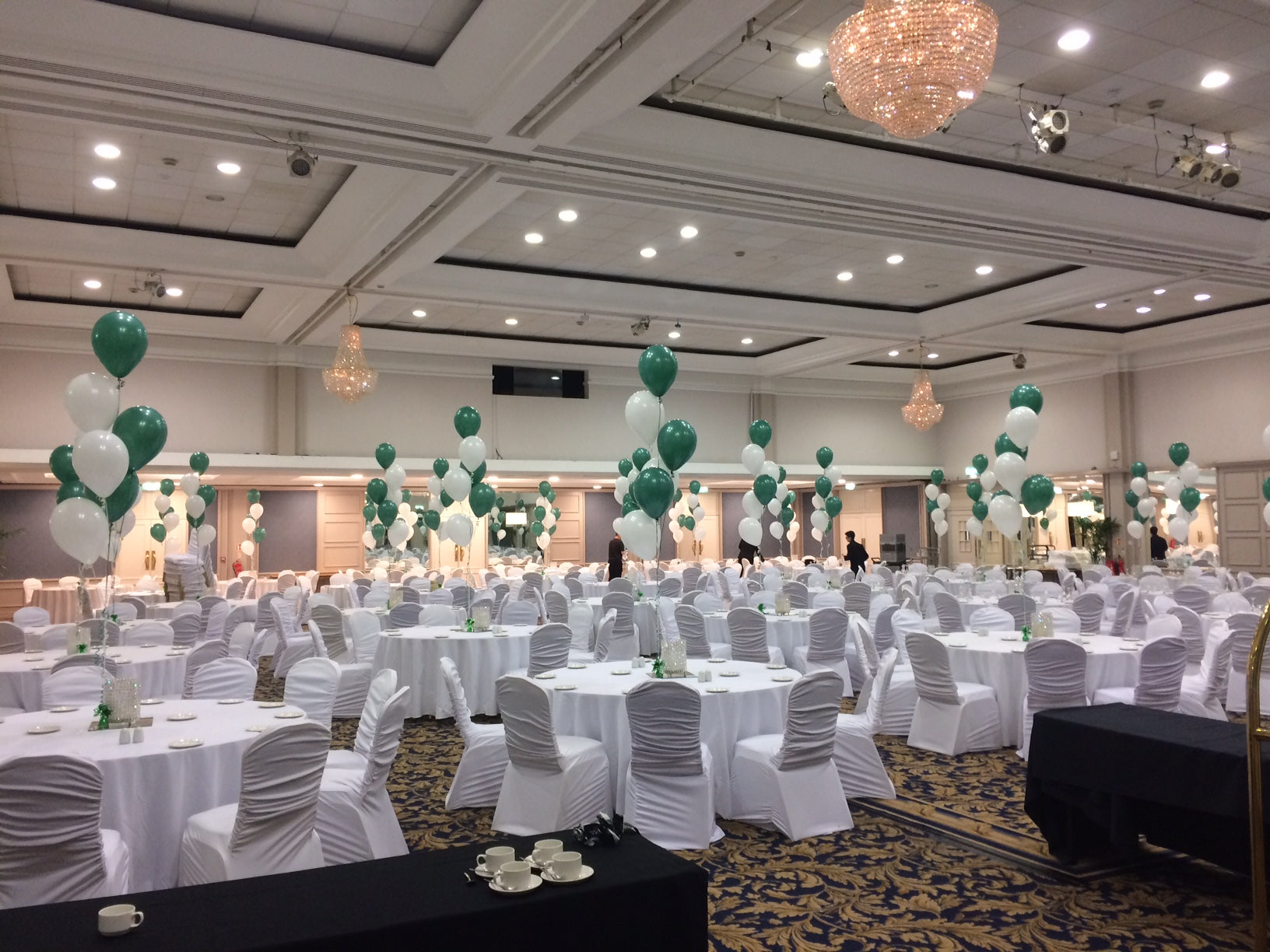 Green and white balloon bouquets on tables in a hotel function room.