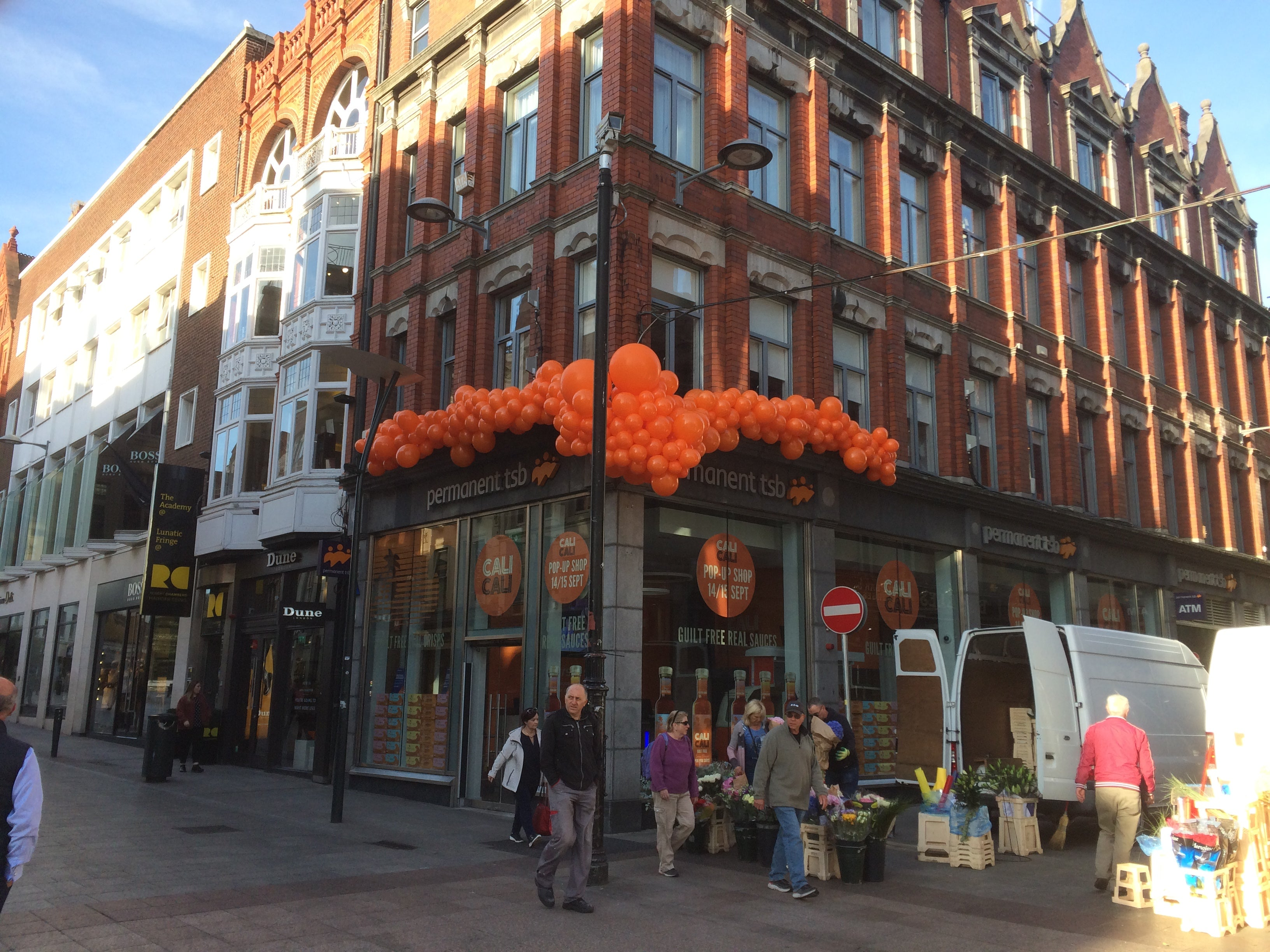 Large orange balloon display on side of building.