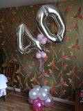 Large forty shaped balloon design in silver and pink standing on floor.