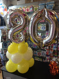Silver number 80 balloon on top of white and yellow balloons.