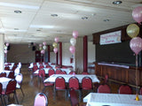 Balloon bouquets and banner at party venue.