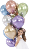 Smiling little girl holding different coloured shiny balloons.