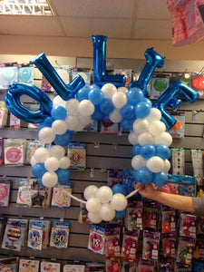 Balloons spelling the name Ollie arranged on a hoop, in blue and white. A hand holds the design in place.