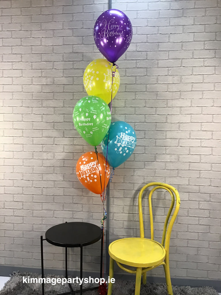 Multicoloured printed helium balloons on a weight.