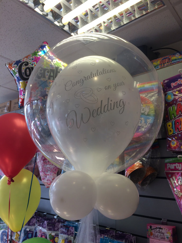 Printed white wedding balloon inside another clear balloon.