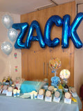 Large helium filled blue letter balloons.